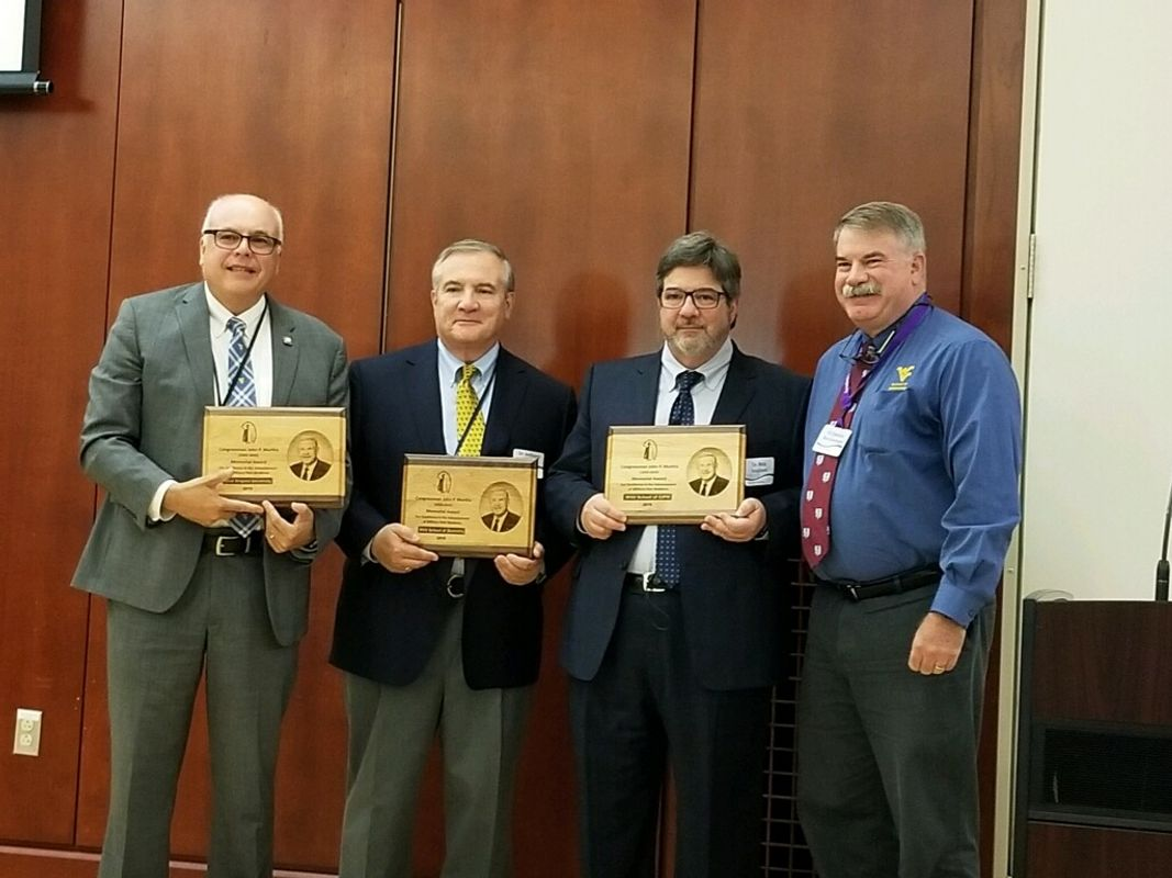 Three men in suits hold awards and one man in button-down shirt poses with them in conference room.